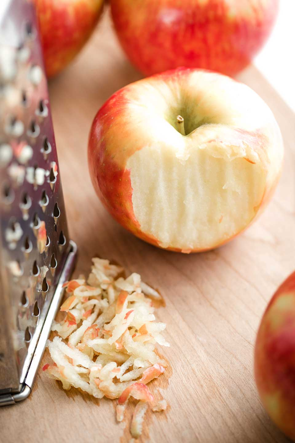 Honey Crisp apple that's been partially grated, sitting on cutting board next to a box grater and a small pile of grated apple