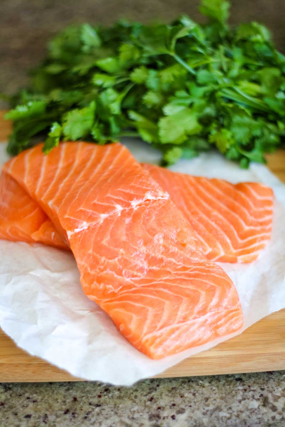 gorgeous fresh salmon filets on butcher paper, with a bunch of fresh parsley in the background