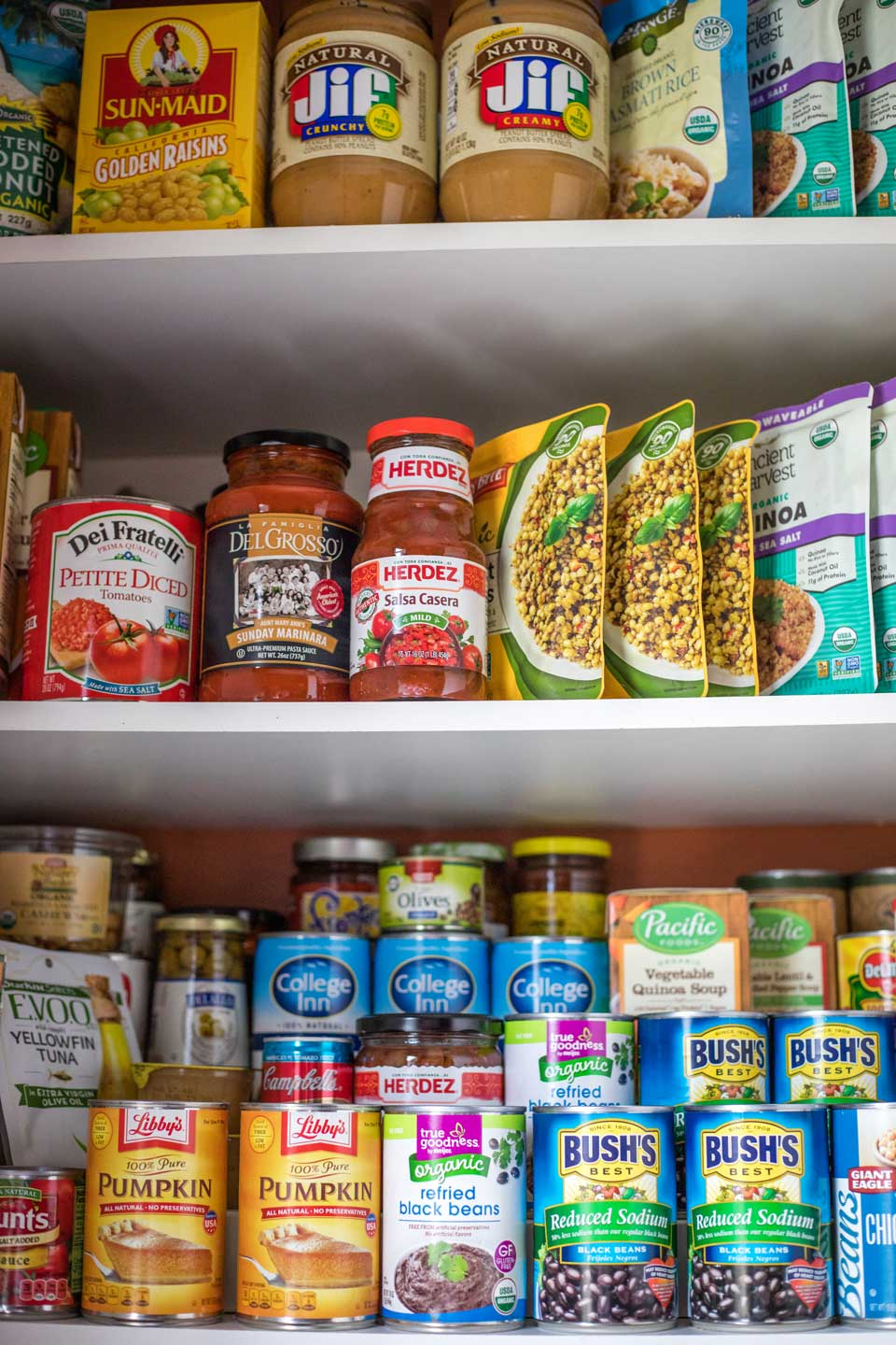 3 pantry shelves stocked with shelf-stable ingredients like canned beans and pumpkin, peanut butter, jarred salsa and pasta sauce, etc.