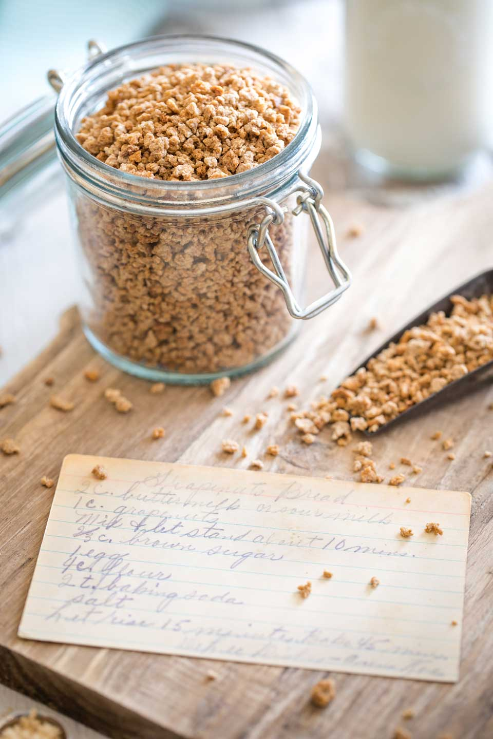 my Grandma's faded, yellowing recipe card laid on a wooden cutting board with a glass canister and scoop of Grape-Nuts cereal nearby and buttermilk in the background