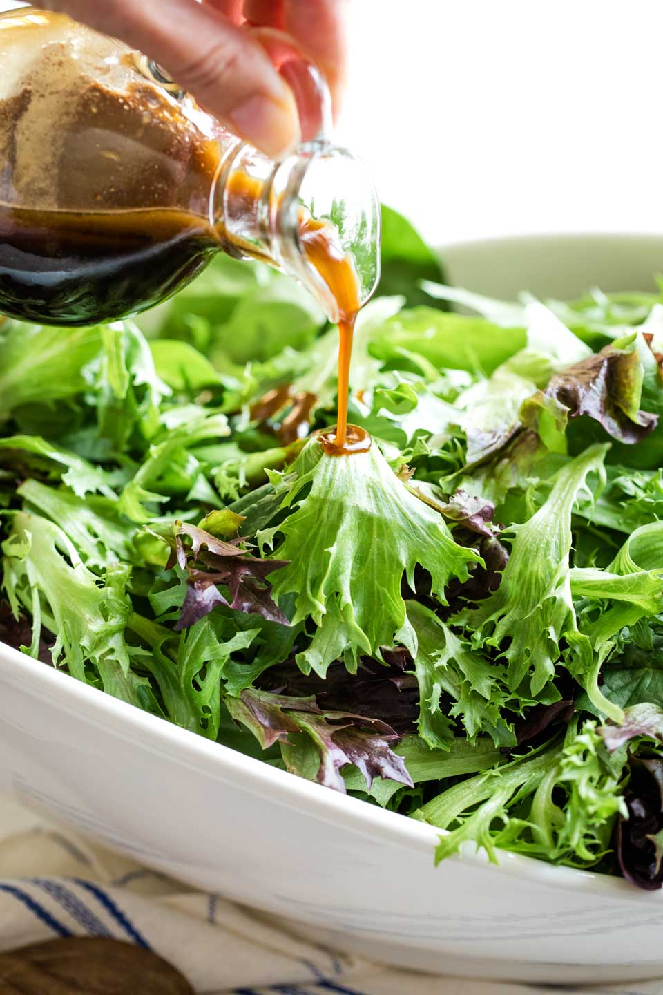 salad greens in large white porcelain bowl, with cruet of balsamic vinaigrette just beginning to be poured in a slow stream over top