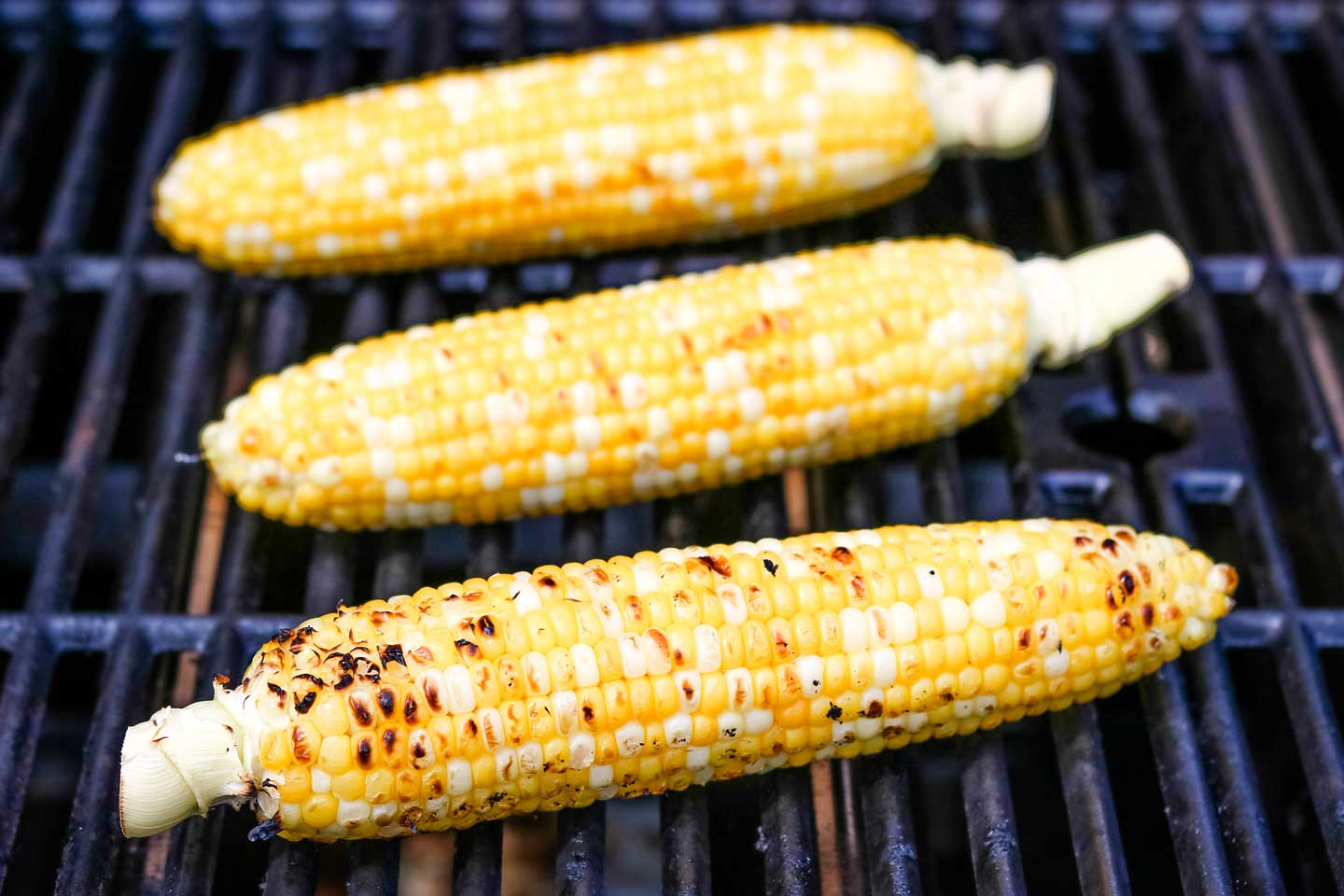 three ears of husked sweet corn on an outdoor grill, with some toasty brown spots developing on them