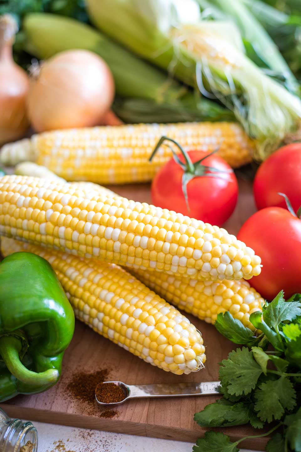 recipe ingredients, uncut on a cutting board - whole ears of fresh sweet corn, tomatoes, a green pepper, onions, and cilantro