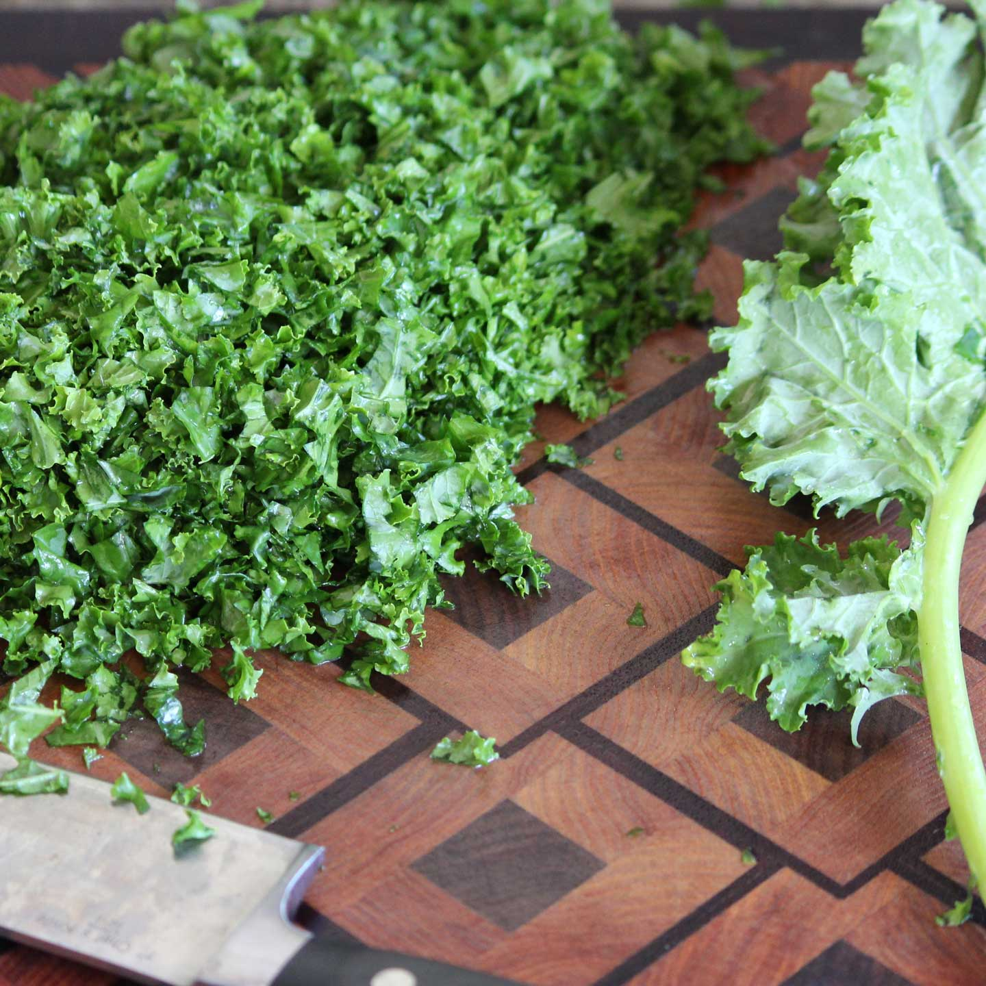 wooden inlay cutting board with a pile of finely chopped kale on one side and a whole kale leaf on the other