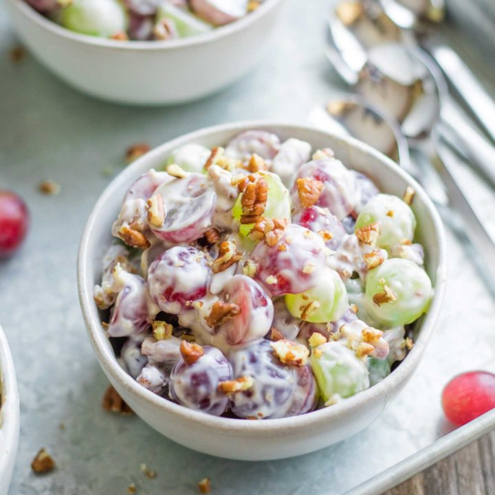 one small serving bowl of grape salad, on a serving tray with spoons and other small bowls in the background