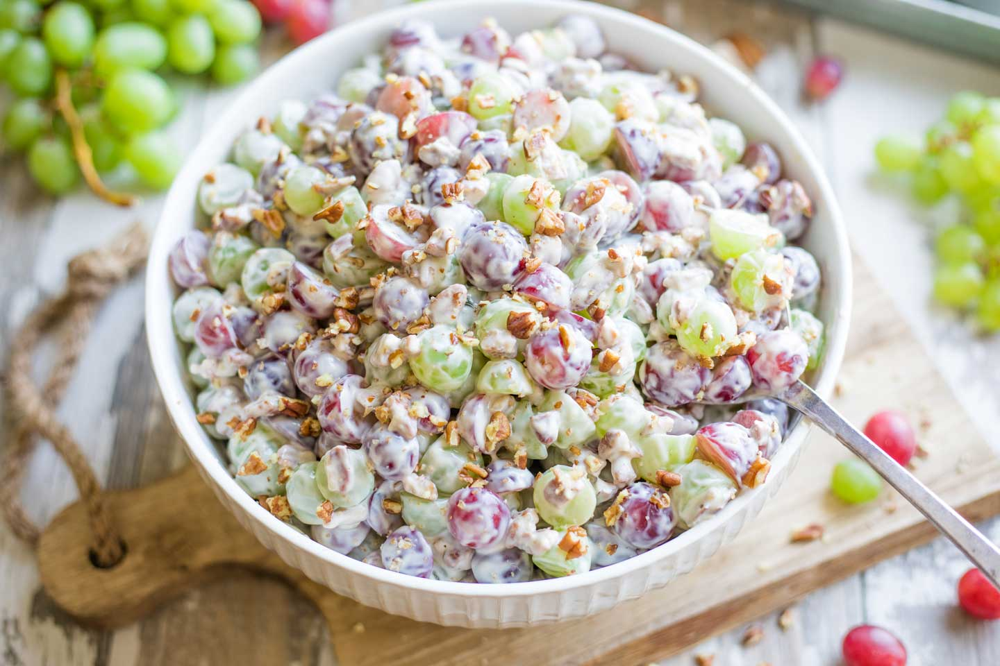 large serving bowl filled with Grape Salad on a wooden board with a big serving spoon dipping in