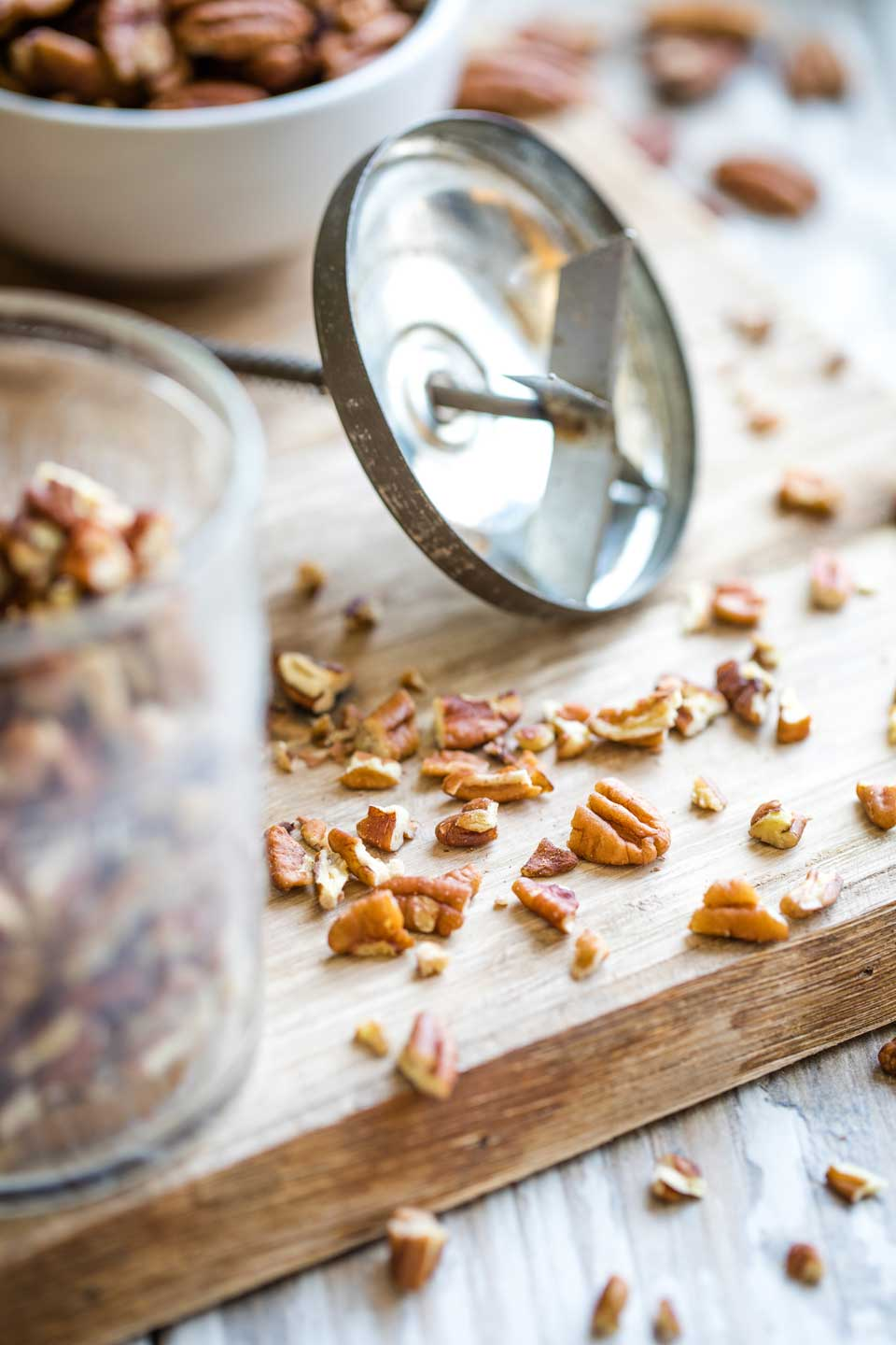 chopped pecans scattered on a cutting board with my Grandmother's antique nut chopper laying alongside