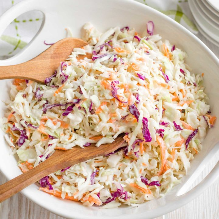 overhead photo of a white serving bowl full of coleslaw, with a wooden serving set scooping into it