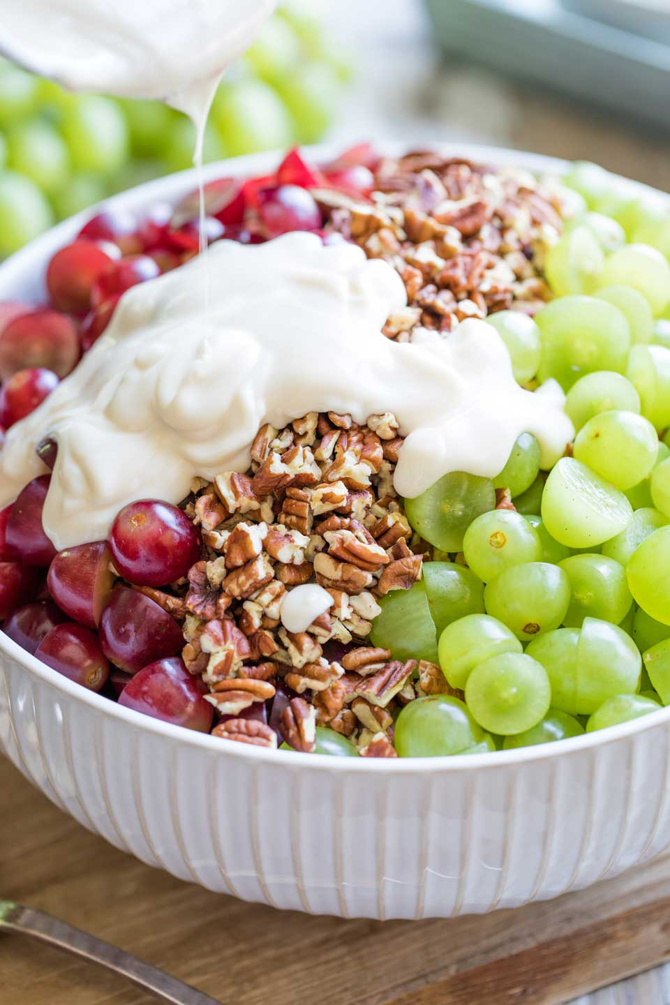 large serving bowl with red grapes to the left, green grapes to the right, and pecans down the middle - with cream cheese dressing being poured on top