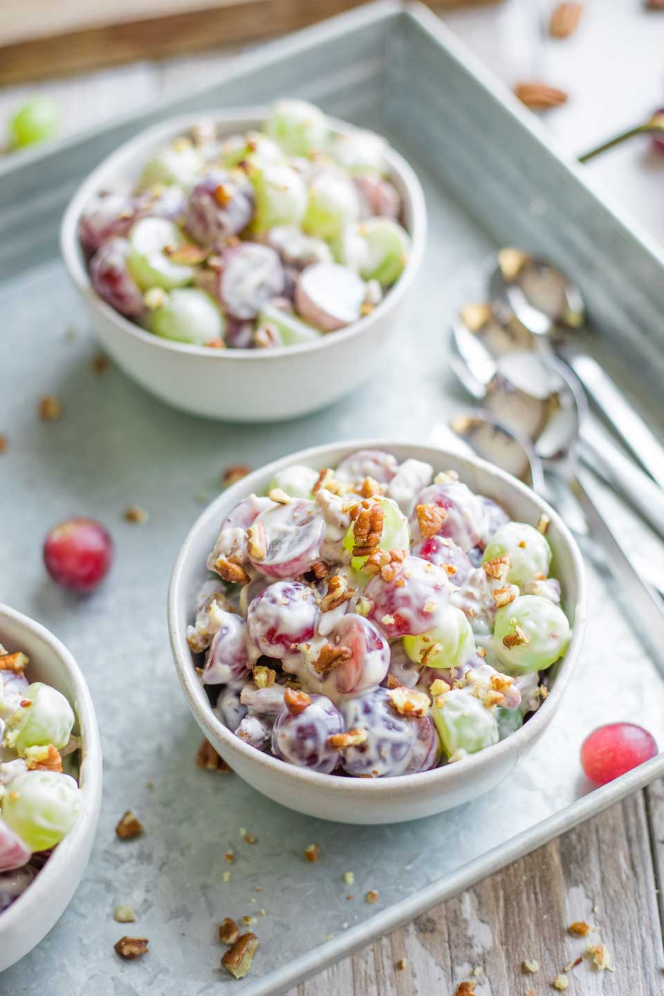 individual bowl of Grape Salad on metal serving tray with spoons and other bowls nearby, ready to be served