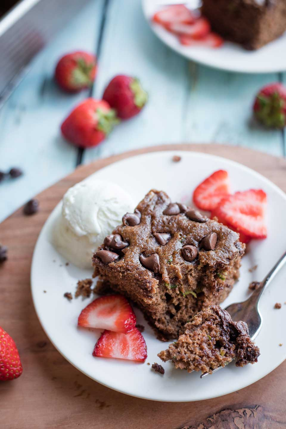 one slice of chocolate zucchini cake on a white plate that's resting on a wooden charger, with strawberry slices and ice cream, with a forkful bite taken out, and extra strawberries in the background