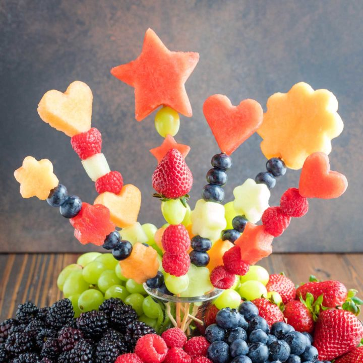 closeup of the fruit kabobs in a bouquet arranged in a glass vase as the centerpiece of a large fruit platter filled with green grapes and different berries