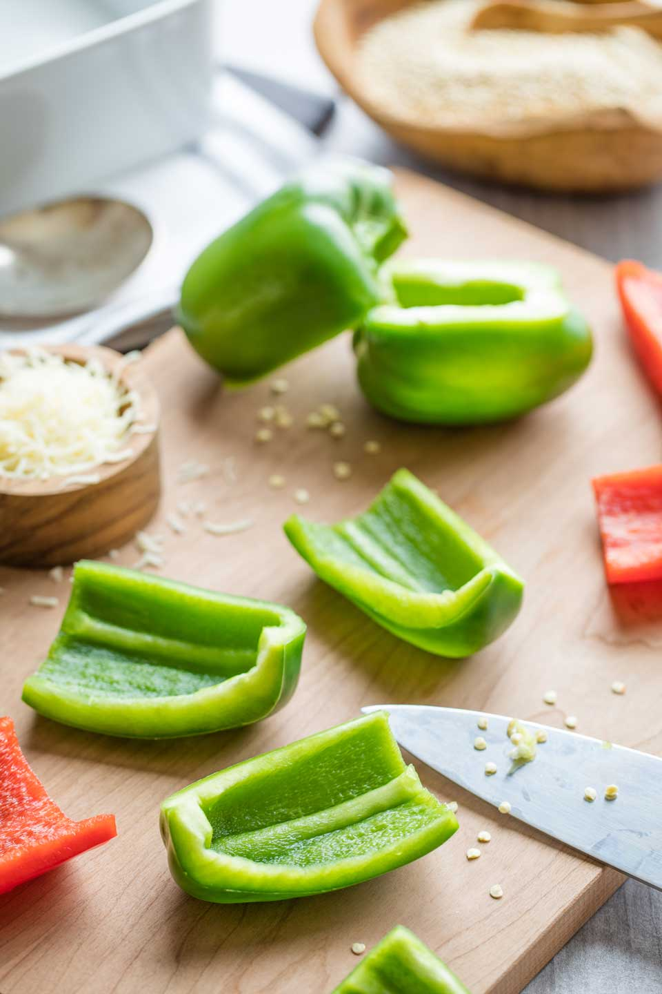 Cutting board with green peppers cut into pieces, with red peppers and cheeses for the casserole also nearby.