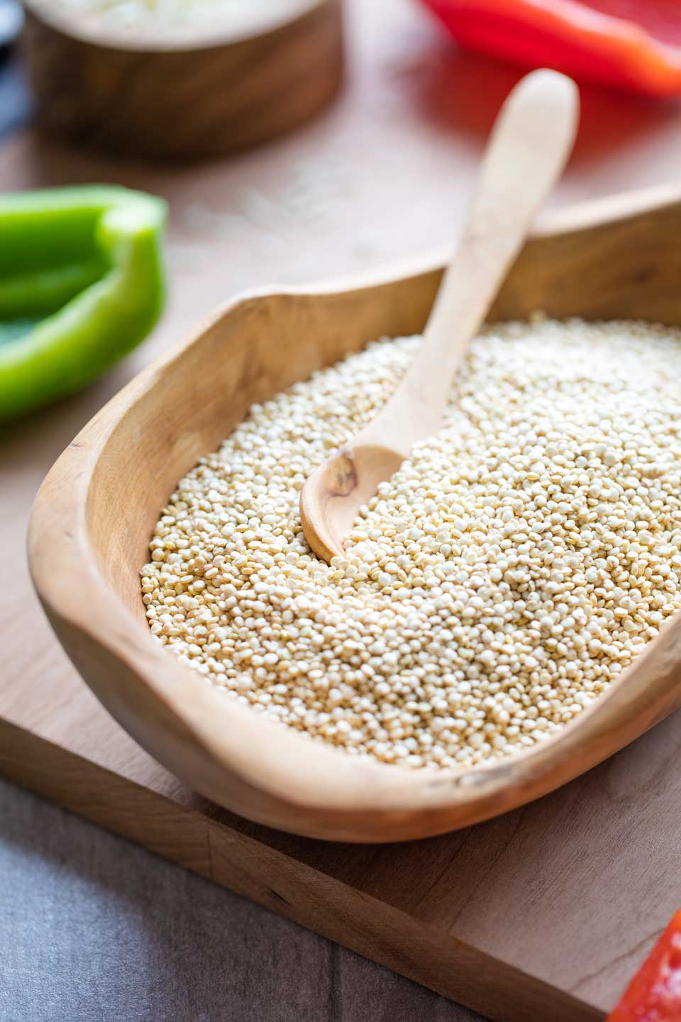 Closeup of a wooden bowl full of uncooked quinoa, with a tiny wooden spoon dipped into it.