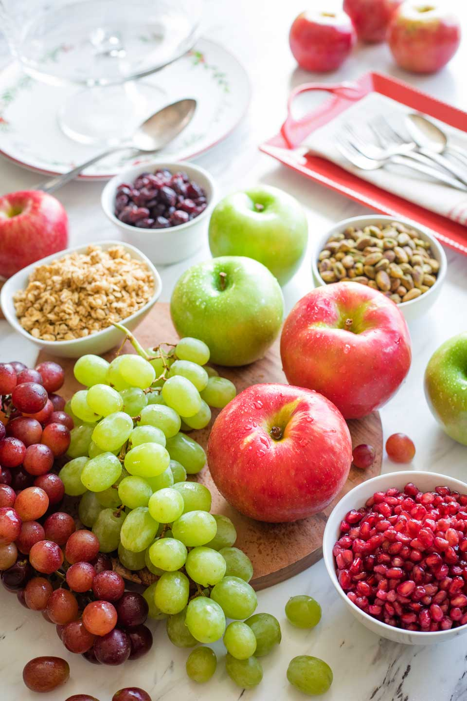 Ingredients like whole apples, bunches of grapes, and bowls of cranberries, granola, pistachios, and pomegranate arils.