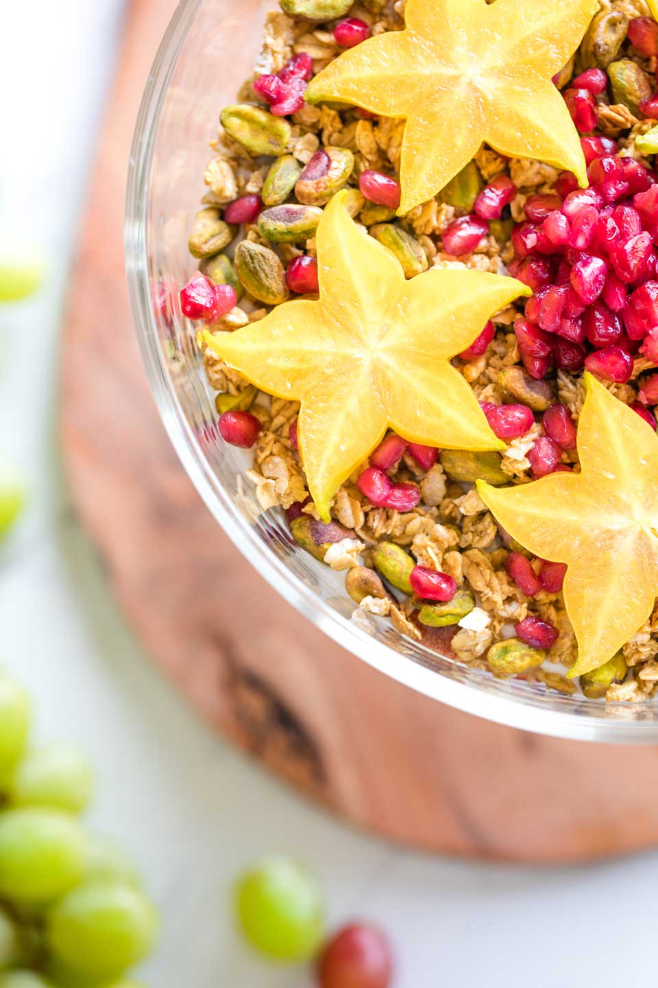 Overhead closeup of three of the starfruit stars on top of the salad, with the trifle bowl sitting on the the cutting board and extra grapes nearby.