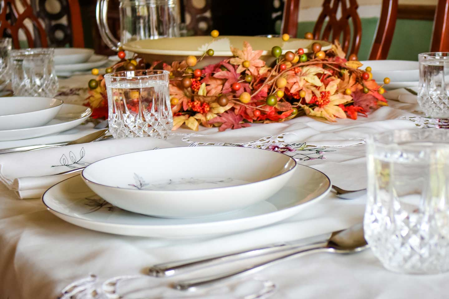 Closeup of a tablescape set for Thanksgiving dinner, with a white tablecloth, china and crystal, and a yellow-and-orange wreath centerpiece.