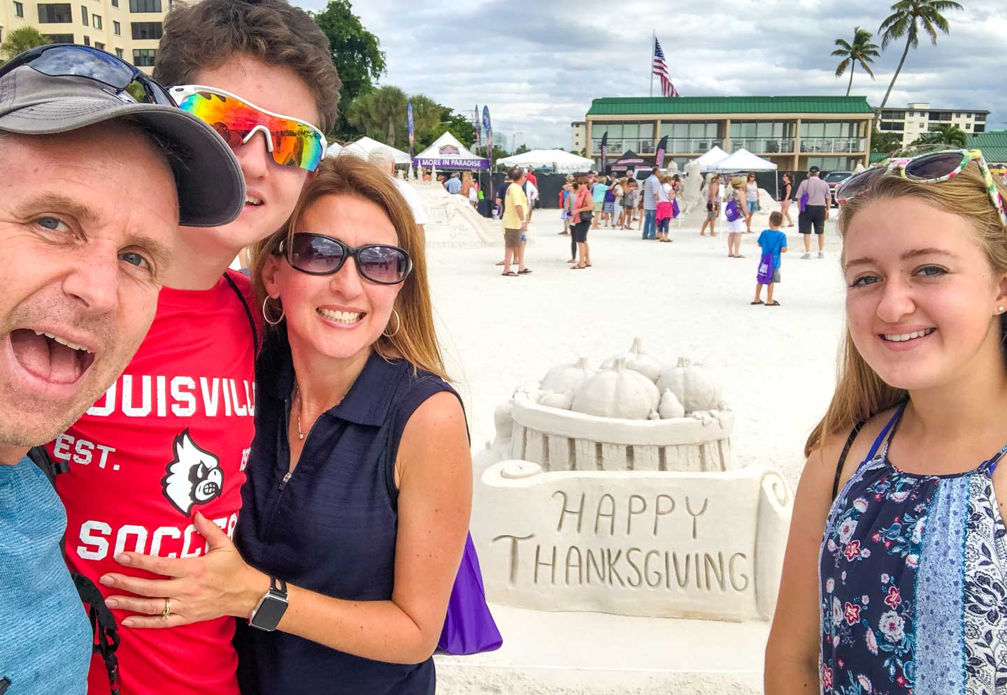 """Family photo of us near a sand sculpture that says """"Happy Thanksgiving""""."""