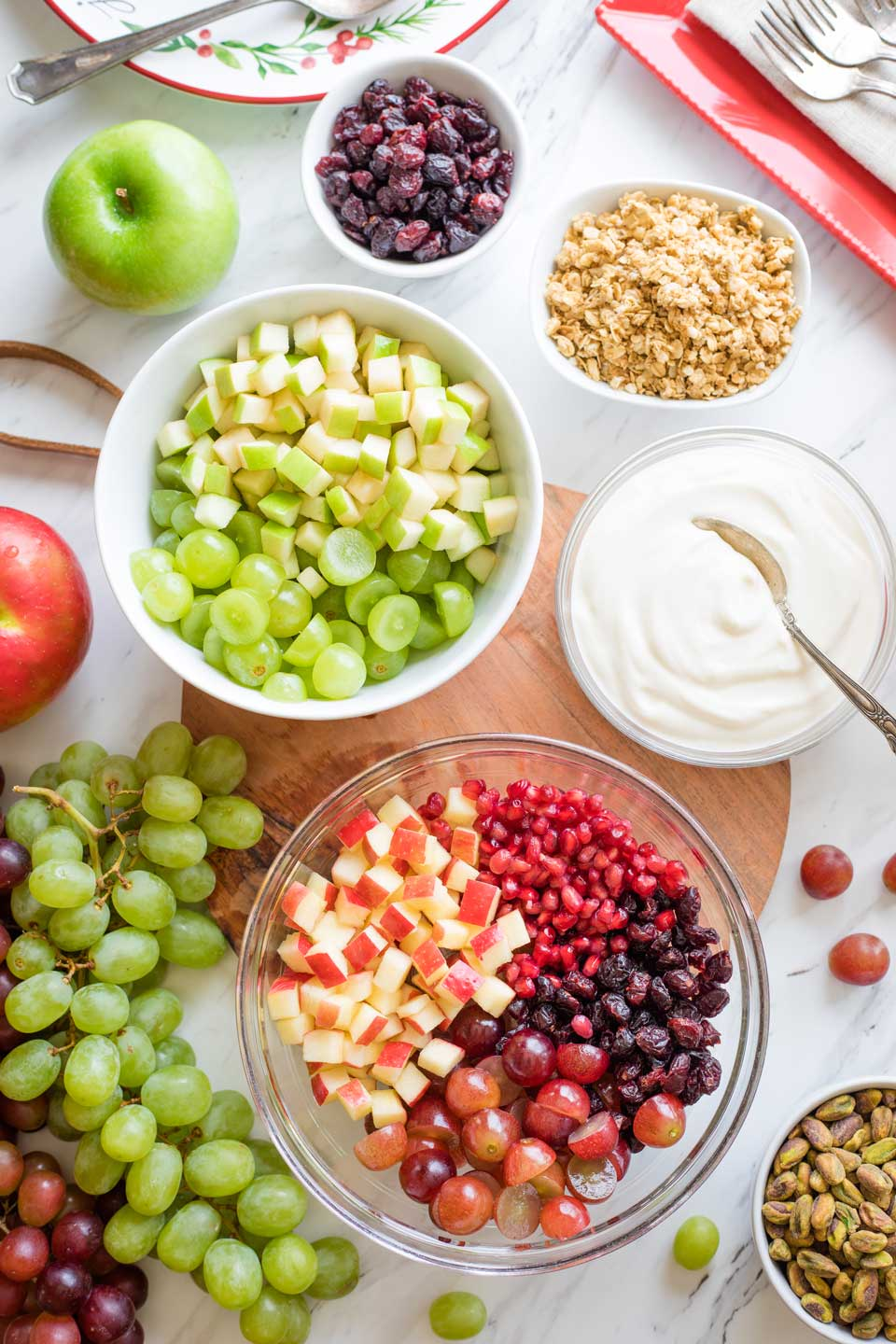 Overhead of prepped ingredients: one bowl of red fruit, one bowl of green fruit, one bowl of fruit salad dressing, plus bowls of pistachios and extra pomegranate arils and cranberries.