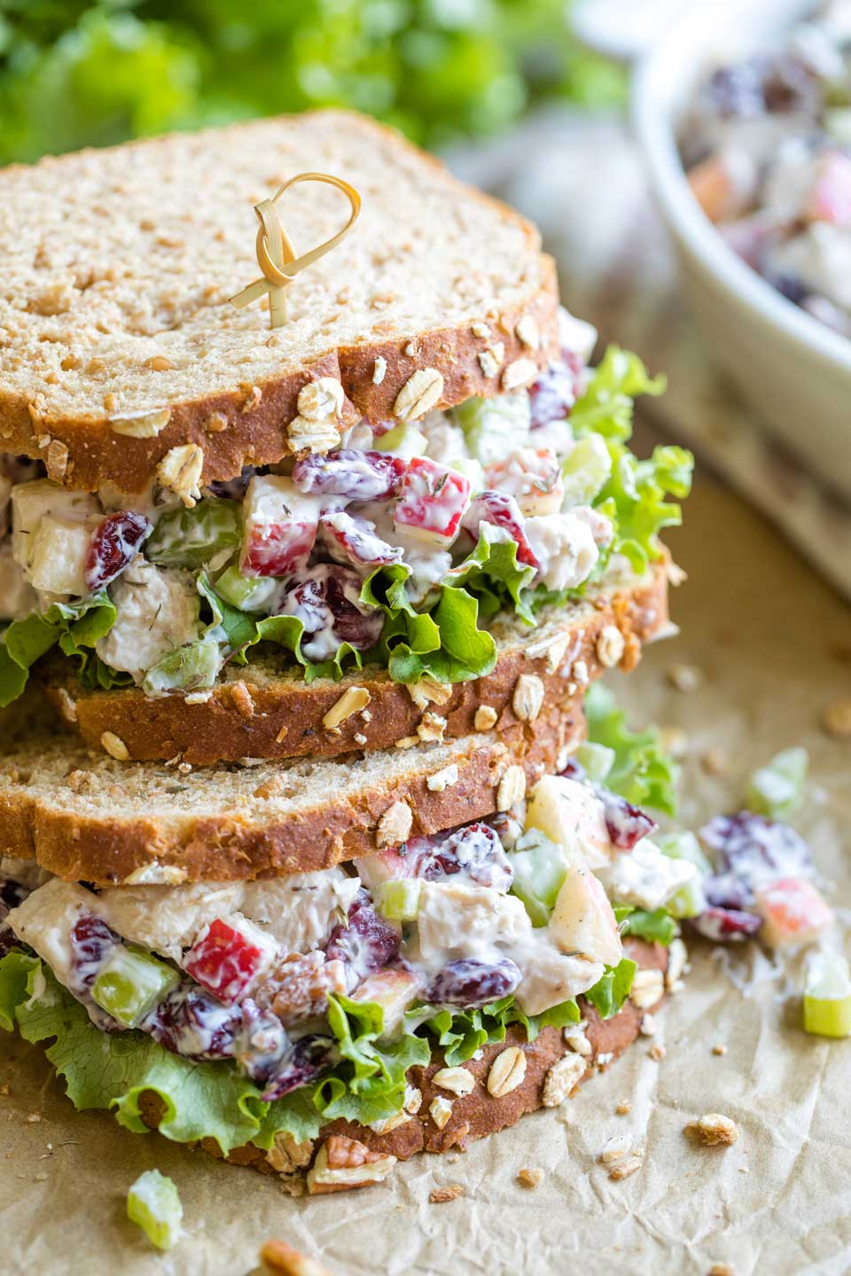 Two finished sandwiches, stacked on top of each other on parchment, with the bowl of extra turkey salad in the background.