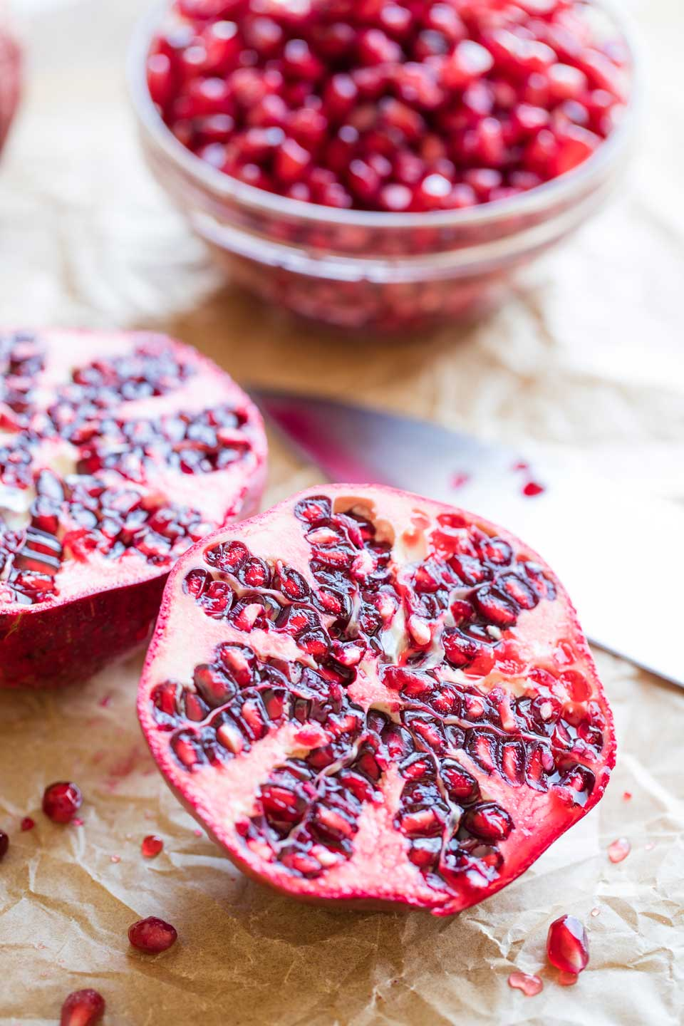 A pomegranate cut horizontally in half, with a bowl full of arils in the background.