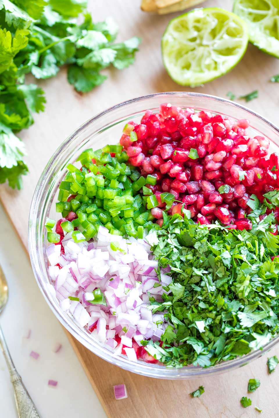 Overhead of a glass mixing bowl on cutting board, filled with the ingredients for this Pomegranate Salsa, separated into quadrants before being mixed together.