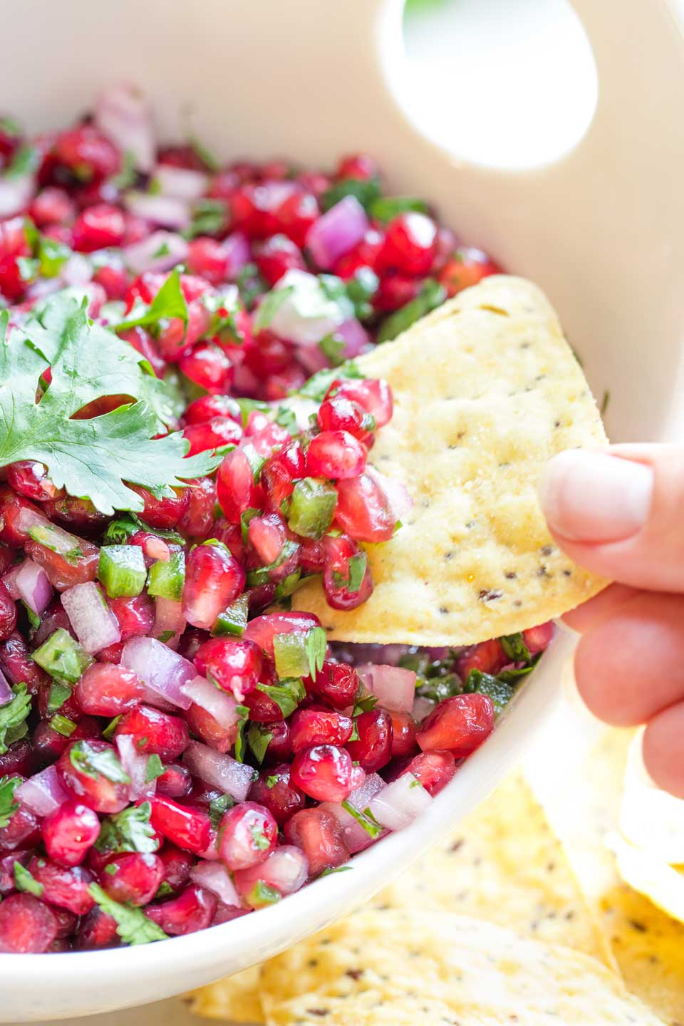 Closeup of fingers dipping a yellow tortilla chip into a serving bowl filled with this salsa recipe.