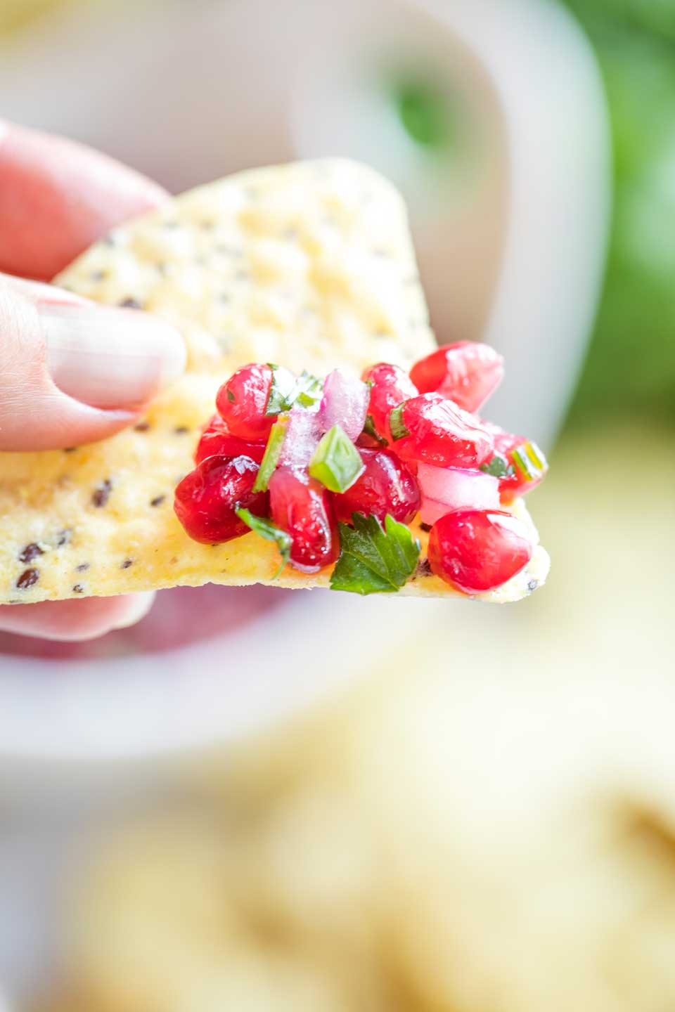 Closeup of fingers holding a tortilla chip with some of the Pomegranate Salsa piled on its tip - the serving bowl and other tortilla chips are blurred out in the background.