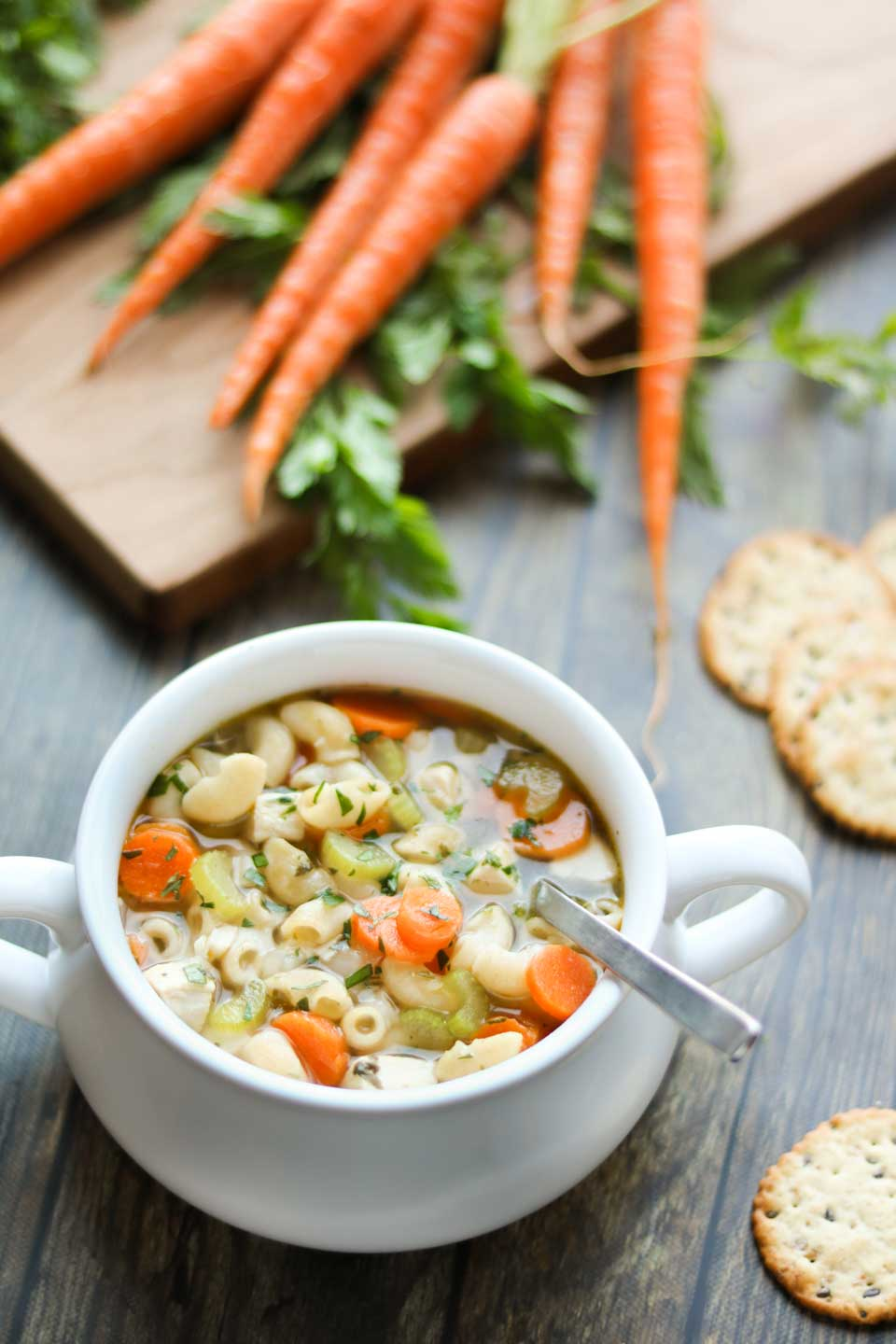 One bowl filled with this soup recipe, with a spoon dipped into it and crackers and pretty, raw carrots in the background.