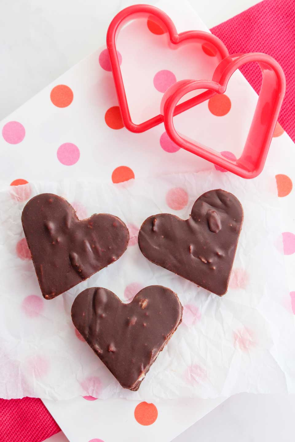 Overhead photo of three fudge hearts, showing how you can easy fudge recipe without condensed milk and, once it has set, cut it into heart shapes with cooke cutters for Valentine's Day.