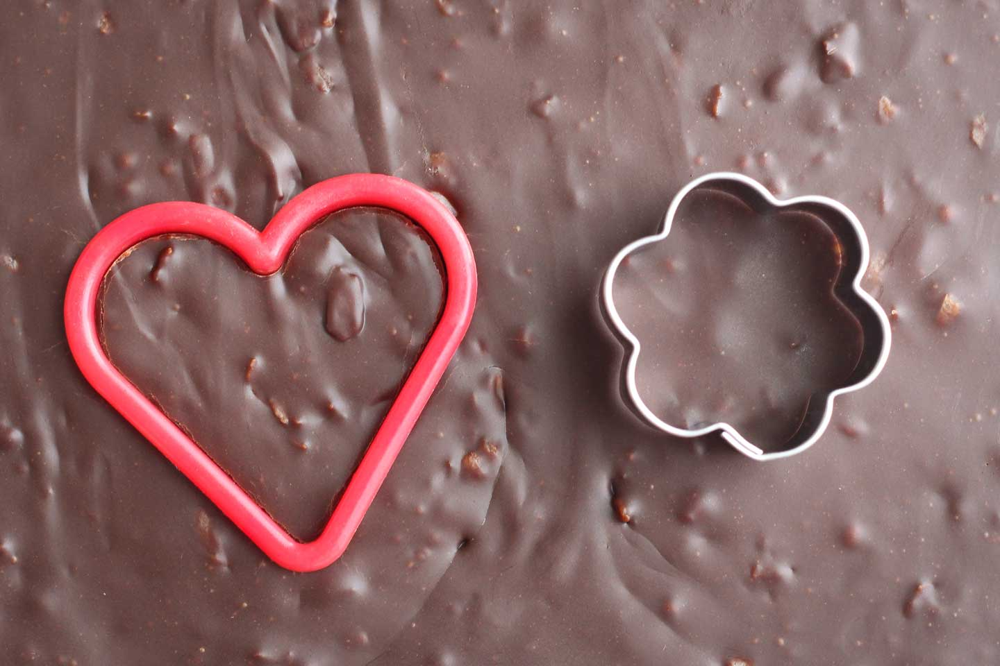 Closeup of two cookie cutters - a heart and a flower - cutting into the top of the finished pan of chocolate fudge.