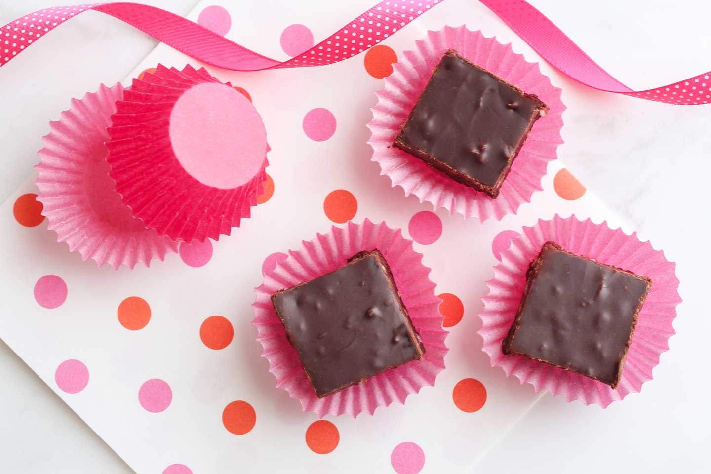 Overhead of three little squares of this fudge recipe, each on a little pink cupcake paper, sitting on a polka-dot background with pink ribbon curling at the top.