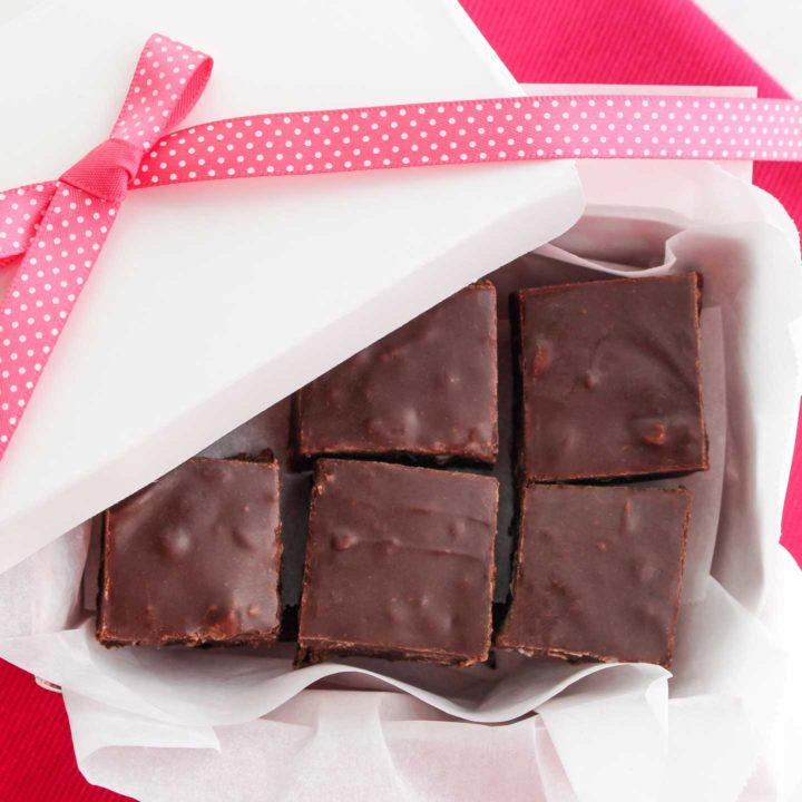 Overhead of squares of chocolate fudge layered in a white gift box, with the lid partially off so you can see the fudge, and a pink polka-dot bow.