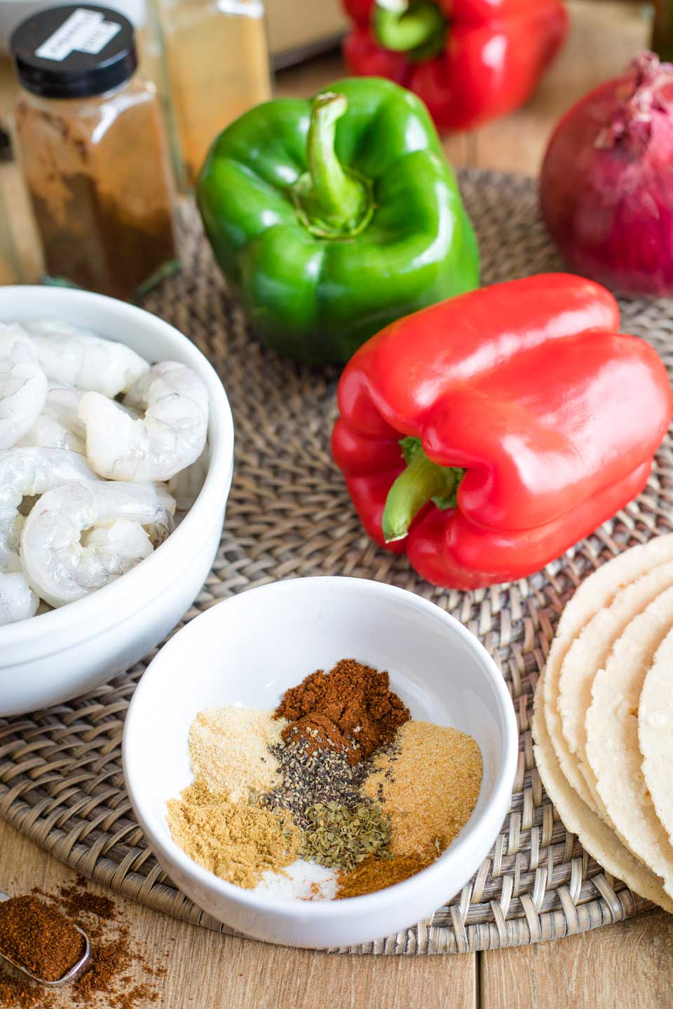 Ingredients to make this shrimp fajitas recipe, including a bowl of spices, raw shrimp, tortillas, peppers, and a red onion.