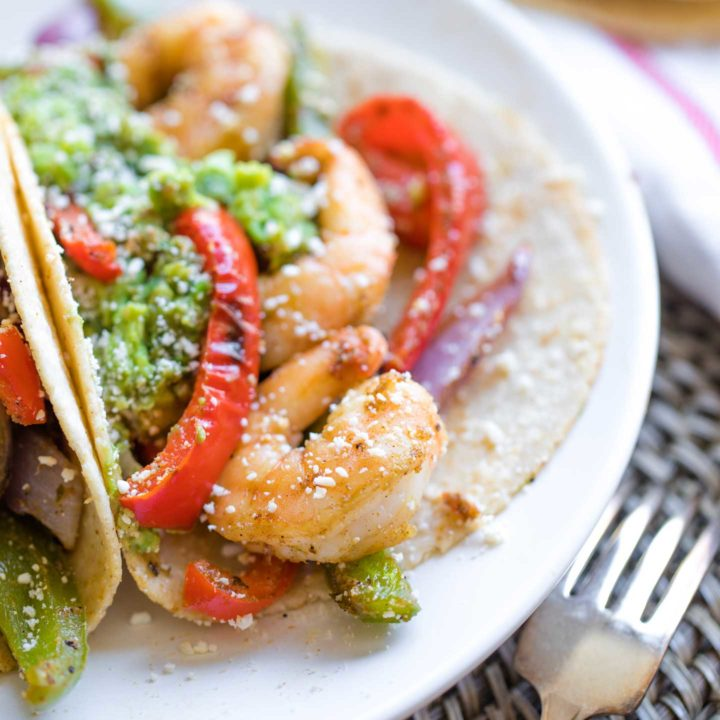Closeup of a Mexican shrimp tucked into a fajita along with other veggies, guac and a dusting of cojita cheese.