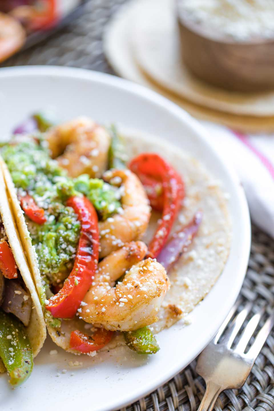 Closeup of one of these fajitas on a plate, so you can see the texture of the shrimp and peppers, with guacamole and sprinkled cheese on top and a fork in the foreground.
