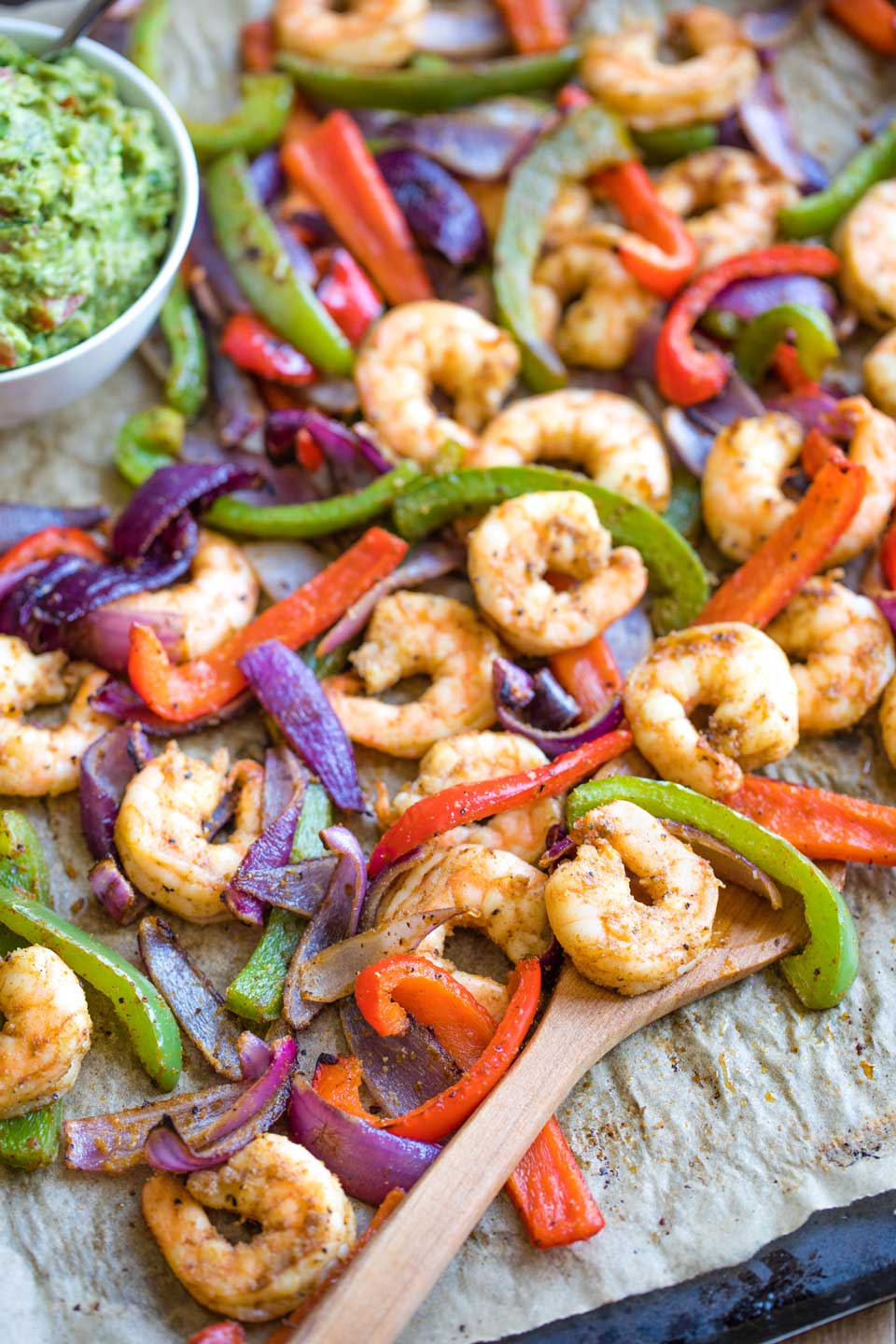 Cooked Mexican shrimp and vegetables, still on the sheet pan, with a wooden spoon scooping in and a bowl of guac nearby.