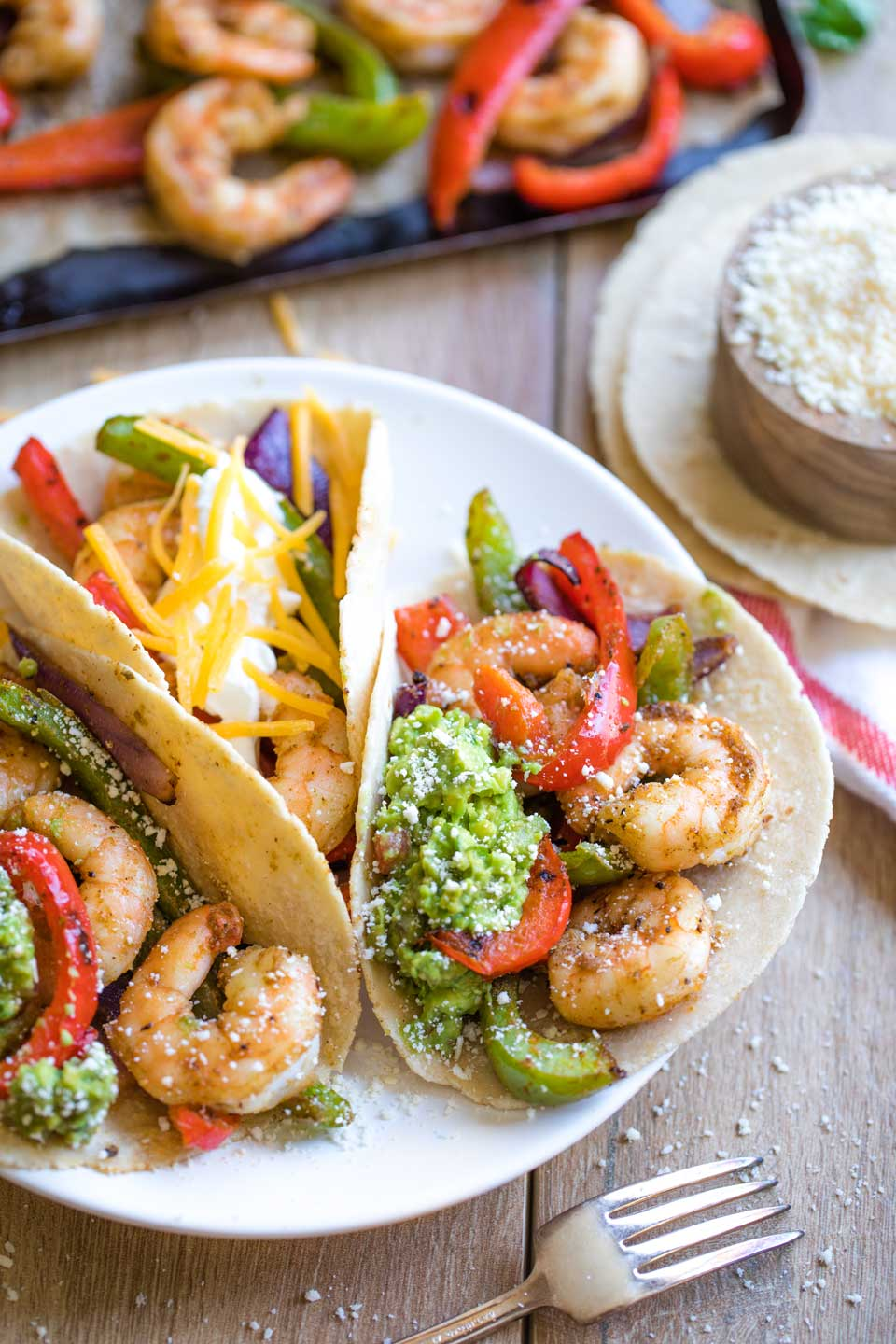 Three shrimp fajitas nestled together on a plate, showing different combinations of fajita toppings you could choose.