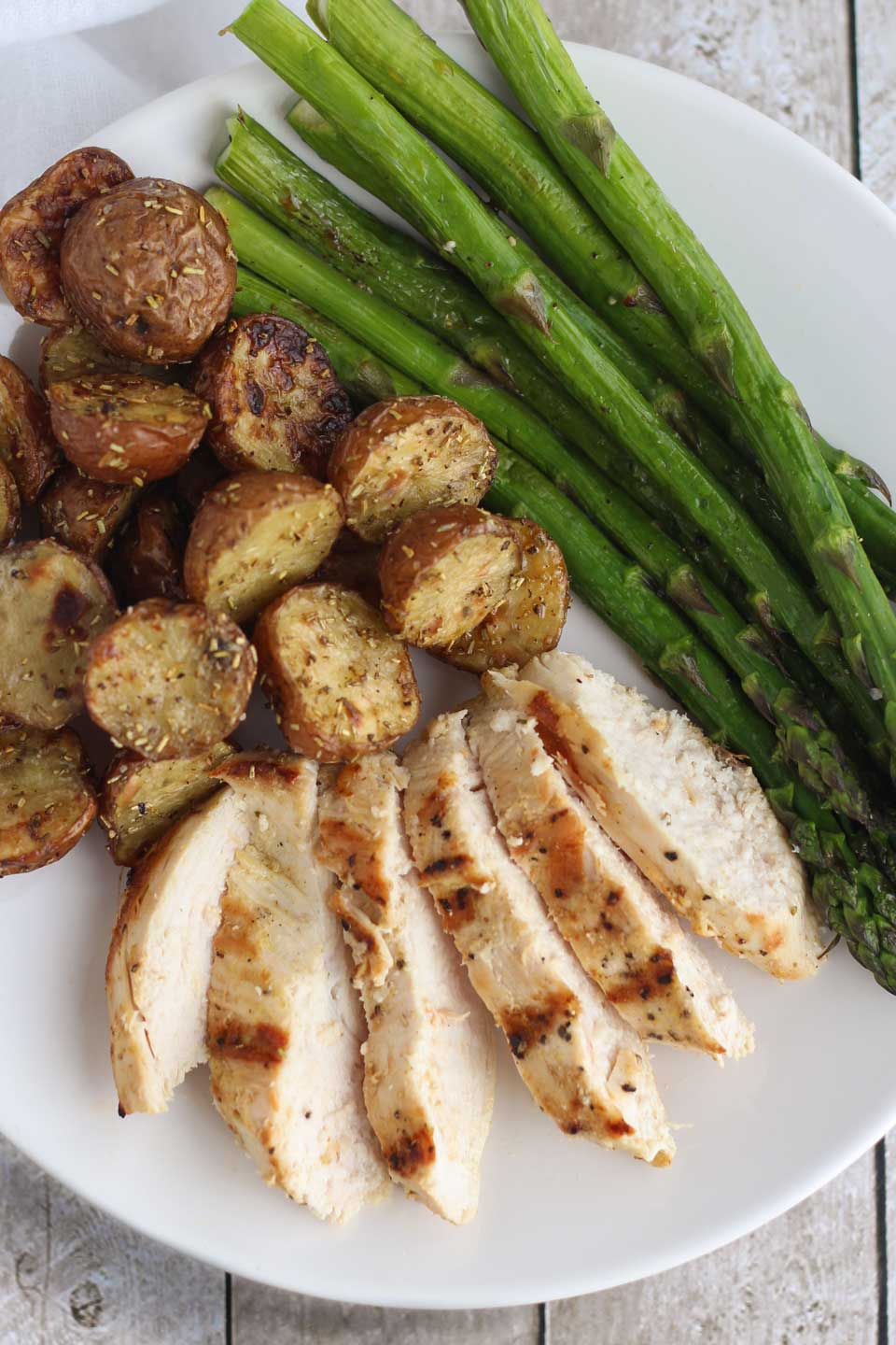 Closeup of a white dinner plate with slices of grilled, boneless chicken breast fanned out and surrounded by asparagus and roasted red potatoes.