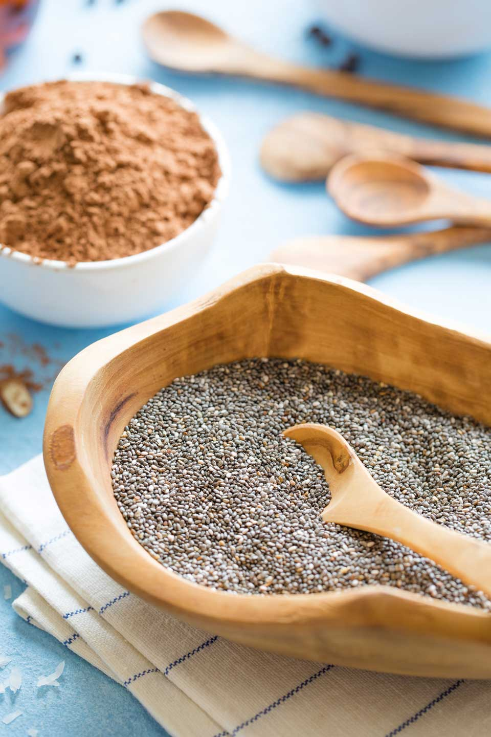 Closeup of a wooden bowl filled with chia seeds, with a white bowl of cocoa powder and wooden spoons in the background.