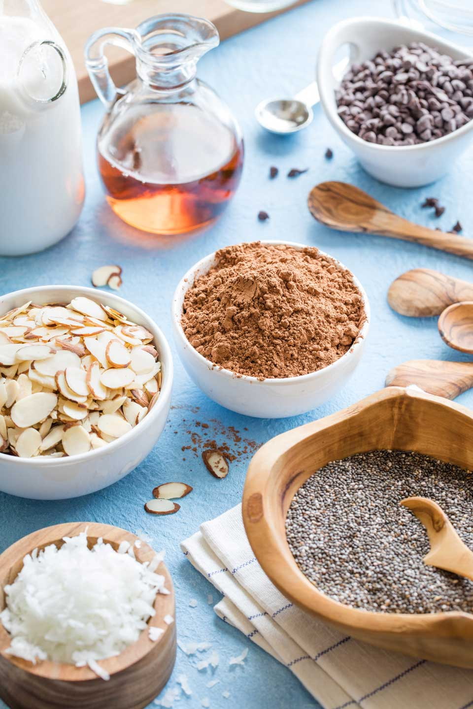 Ingredients to make the recipe - chocolate chips, chia seeds, cocoa powder, coconut, almonds, etc. - arranged in little bowls.