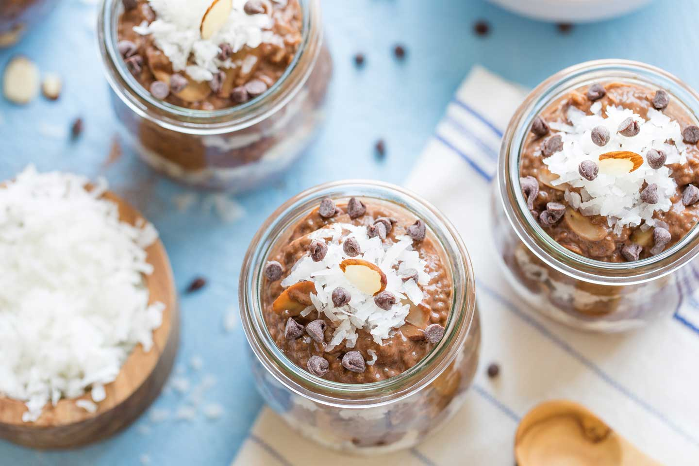 Overhead shot of three little glass meal prep jars layered with chia pudding, sprinkled with chocolate chips, coconut and almonds - with a wooden bowl of coconut alongside.
