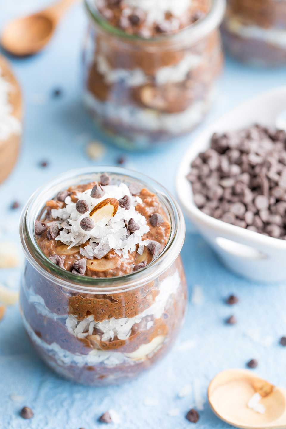 One jar of layered pudding in the foreground, with a bowl of chocolate chips and additional jars of chia pudding in the background.