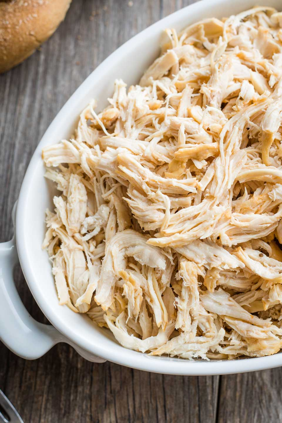 Closeup of a white oval dish filled with shredded chicken breast meat, ready to use in a recipe.