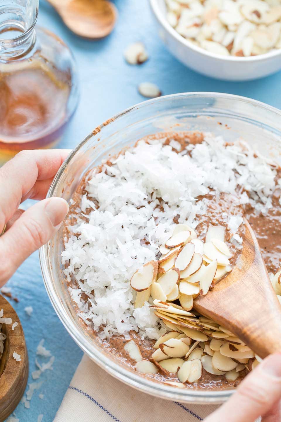 Hand holding a glass mixing bowl with chocolate chia pudding in the bottom, covered with a lavyer of shredded coconut and sliced almonds that are just being mixed in with a wooden spoon.