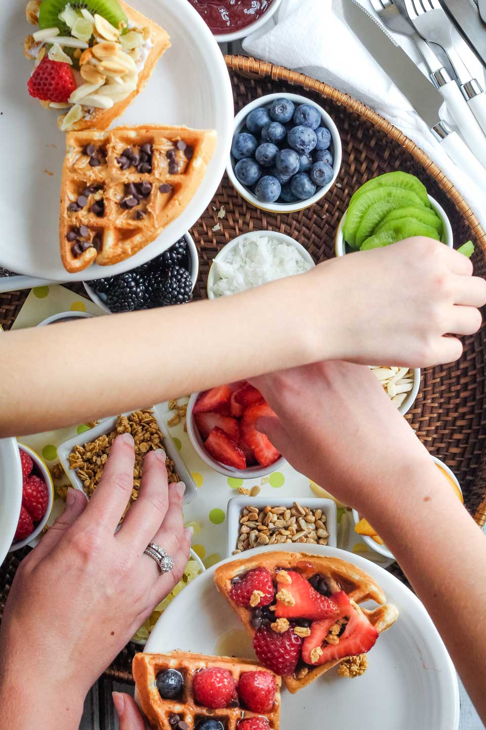 Overhead photo of three hands reaching across each other to load up plates of Galentine's Day waffles with various toppings and sprinkles from a waffle bar.