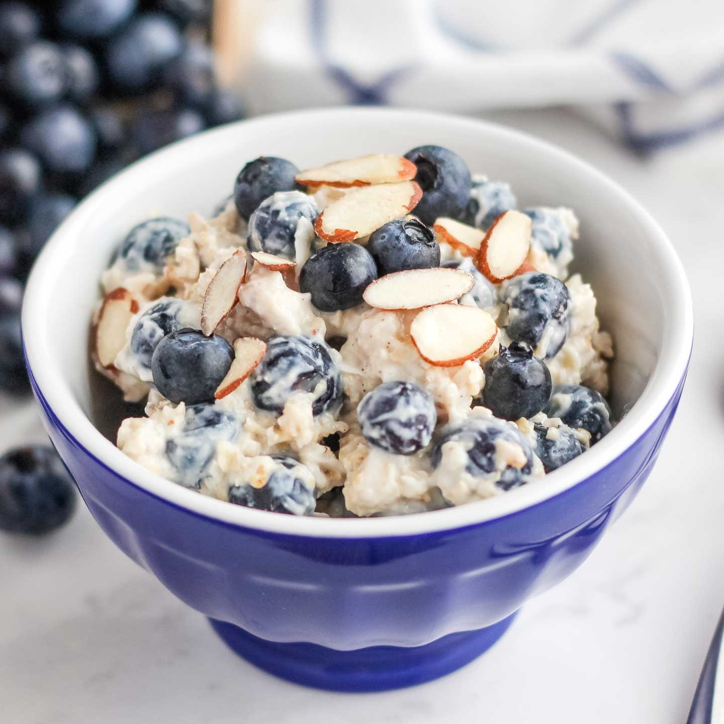 Closeup of a single serving of this cold oatmeal in a little blue bowl, with a blue-striped towel and additional blueberries in the background.