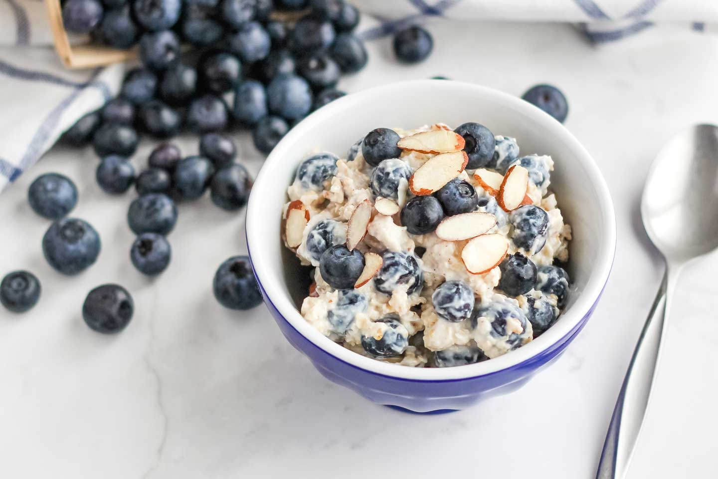 A little blue serving bowl filled with this oats recipe, with a spoon and a cascade of extra blueberries alongside.