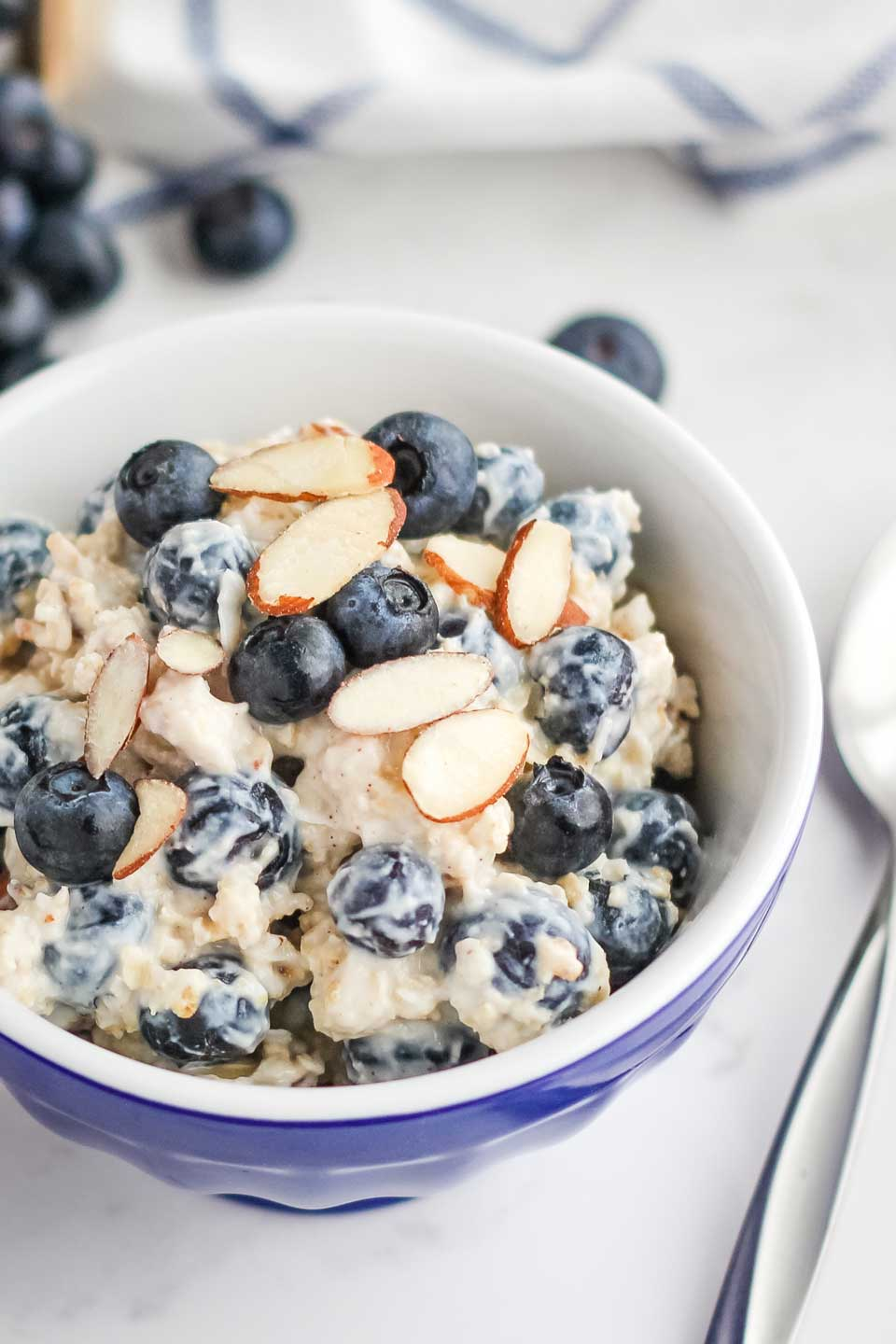 The finished recipe presented in a little blue bowl with a sprinkling of extra blueberries and sliced almonds on top of the cold oats mixture, with a spoon alongside..