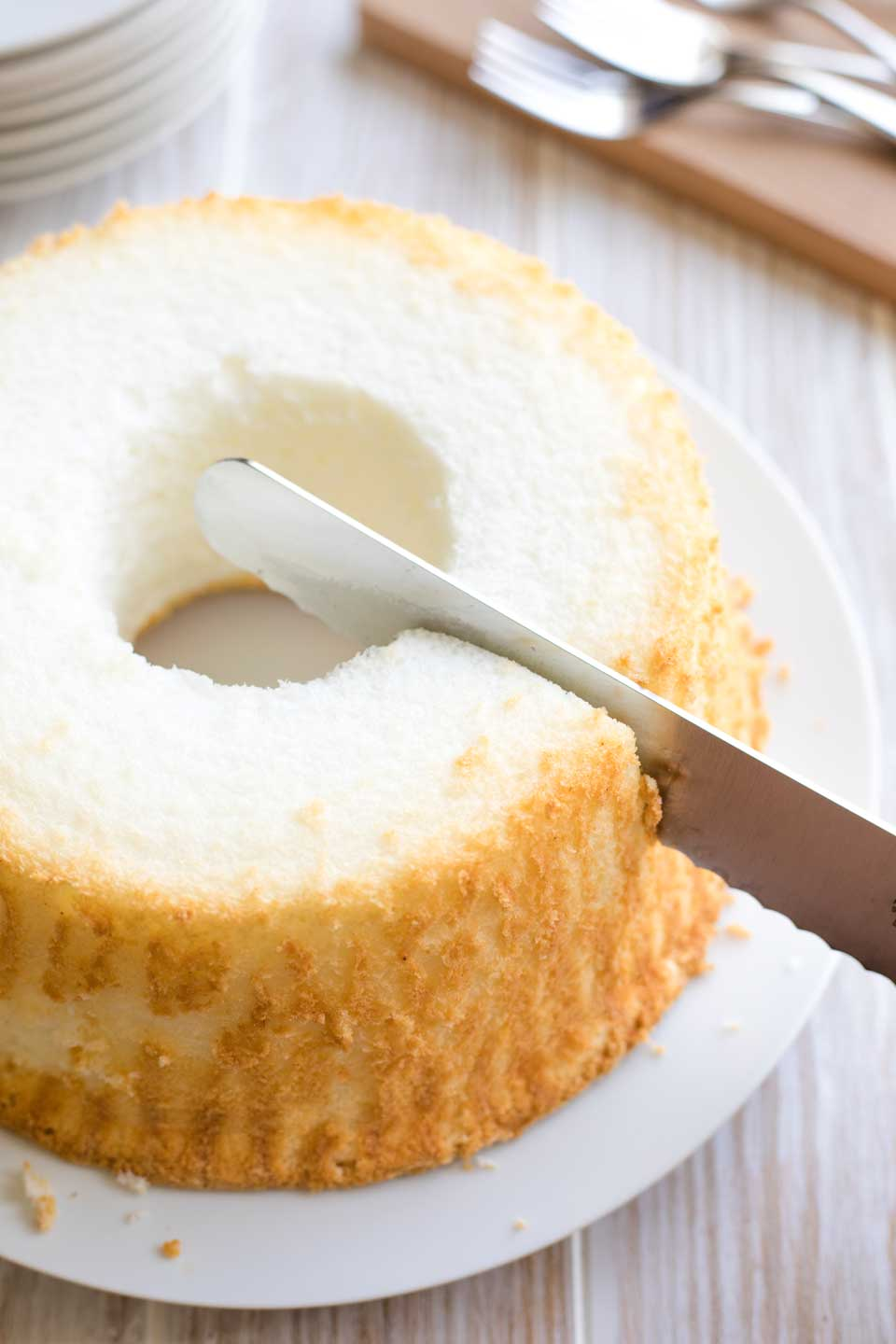 White platter holding an entire angel food cake, with a long serrated knife just starting to make the first cut into it.